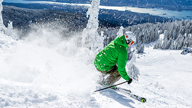 skiier with green jacket going down the run