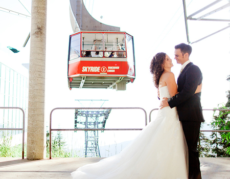 Couple on wedding day in front of Grouse Mountain's red Skyride