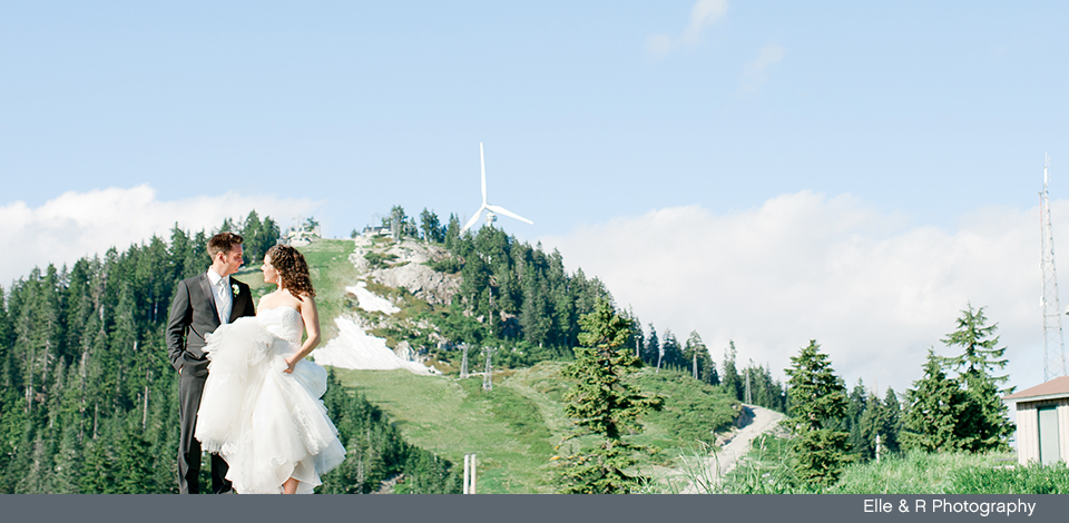 couple in the summer at Grouse Mountain with The Eye of the Wind behind them