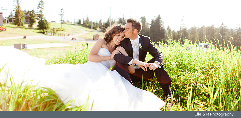 Couple sitting in the grass at Grouse Mountain on their wedding day