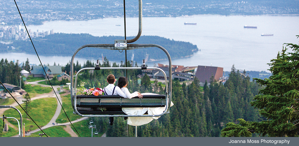 wedding day couple riding chairlift down to Chalet with view of Vancouver in background