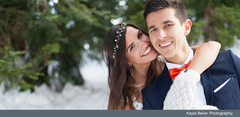 couple smiling in the snow on their wedding day