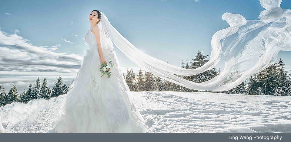 bride at the top of Grouse Mountain in the winter with veil blowing in the wind