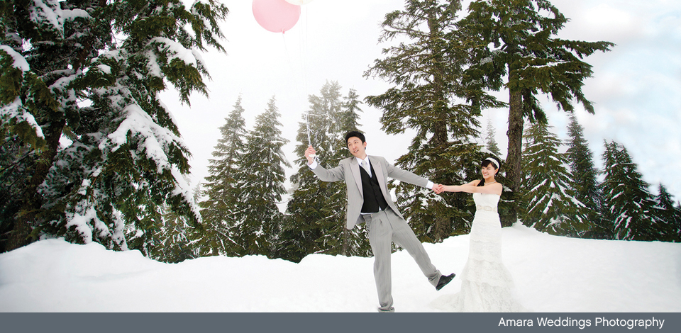 Wedding couple in the snow with pink balloon at Grouse Mountain