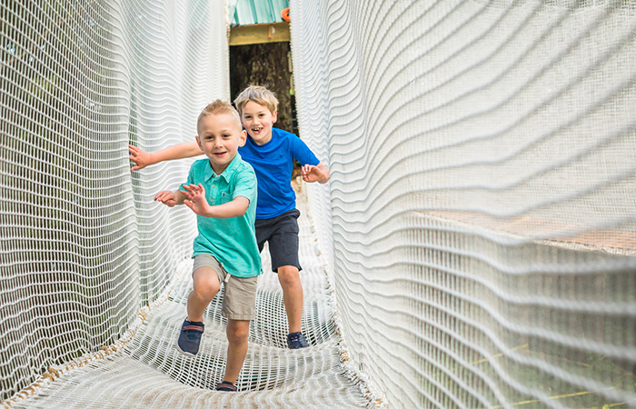 Kids running in new aerial ropes playground made for children