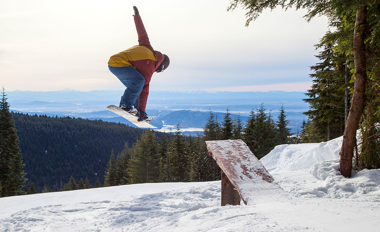 Snowboarder jumping in Grouse Woods™